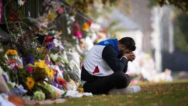 Deepak Sharma takes a quiet moment of contemplation at a makeshift shrine of flowers at the Botanical Gardens in Christchurch, 17th March 2019.