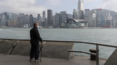 A man looking out Victoria Harbour in the very quiet and empty Tsim Sha Tsui Promenade in Hong Kong.