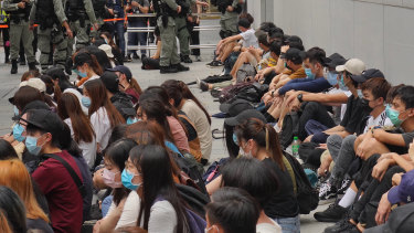 Riot police guard arrested anti-government protesters in the Central district of Hong Kong.