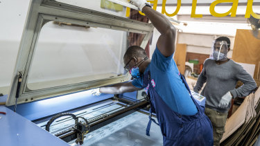 Mohamed Gueye, centre, and Idrissa Sall, right, use a laser cutter to make protective face shields.