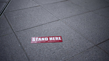 Stand Here signage sits on the sidewalk outside a restaurant in Washington, DC.