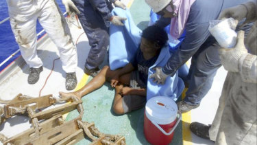Aldi Novel Adilang on the deck of a Panamanian-flagged vessel, MV Arpeggio after being rescued.