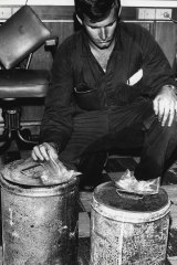 A detective examines two petrol drums found in the foyer of Brisbane's Whiskey Au Go Go.