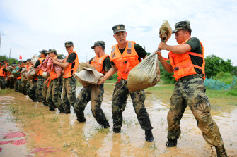 Paramilitary police form a line to move sandbags to reinforce a dyke along the banks of Poyang Lake in Poyang County in eastern China's Jiangxi province on Sunday.