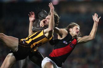 Essendon's Archie Perkins takes down Jack Scrimshaw of the Hawks.