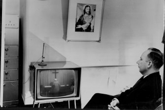 The Reverend Ted Noffs watches a closed circuit screen at the Methodist Wayside Chapel from his office, in 1964, where artist Tiiu Reissar painted him for the Archibald Prize.