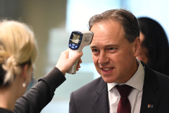 Federal Health Minister Greg Hunt has his temperature checked before touring the Royal Melbourne Hospital on Thursday.