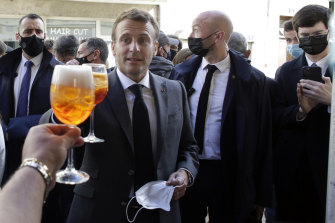 French President Emmanuel Macron, right, and Nevers mayor Denis Thuriot, left, drink with shopkeepers during a visit to mark the reopening of cultural activities after closures during the COVID-19 pandemic, in Nevers, central France.