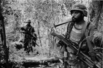 PNG army troops on patrol in heavy jungle in 1997, hunting for guerillas who had shot a boy dead nearby.