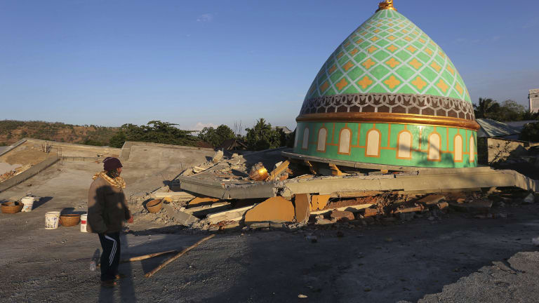 Locals view the devastation of a collapsed Jamiul Jamaah Mosque in Bangsal, North Lombok, Indonesia.