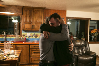Tyler Johnson, right, whose wife, Christina Langford Johnson, was among those killed in an ambush, embraces a family member.