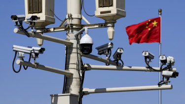 A Chinese national flag flutters near the surveillance cameras in Tiananmen Square in Beijing on Friday. Chinese Premier Li Keqiang denied Beijing tells its companies to spy abroad.