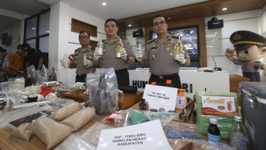 National police spokesman Brigadier general Muhammad Iqbal, centre, shows ammunition, explosive-making materials and other evidence confiscated from suspected militants.
