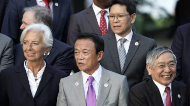 Japan's Finance Minister Taro Aso, centre, stands with IMF Managing Director Christine Lagarde, left, and Bank of Japan Governor Haruhiko Kuroda, at the G20 finance ministers event.