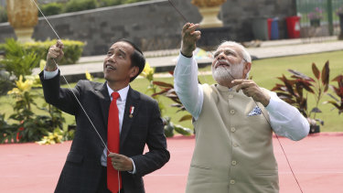 Indonesian President Joko Widodo, left, flies a kite with Indian Prime Minister Narendra Modi during the India-Indonesia kite exhibition in Jakarta.