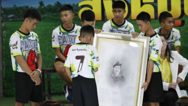 Coach Ekkapol Janthawong, left, and some of the 12 boys paid tribute to a slain diver after their rescue.