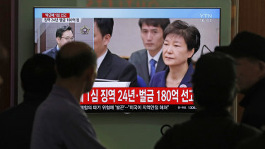 People watch a TV screen showing file footage of former South Korean president Park Geun-hye during a news program on Friday.