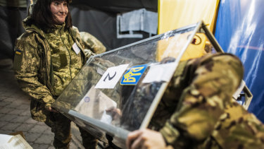 Ukrainian government soldiers, members of the local election commission, open a ballot box in a tent using as a polling station.