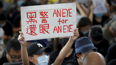 "A woman protests police violence with a placard that reads ""Black police, Return eye,"" during a sit-in at the Hong Kong International Airport arrivals hall."