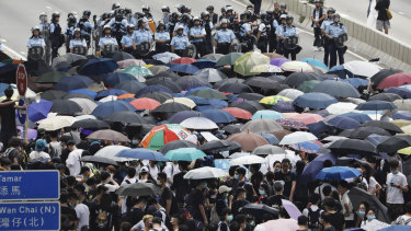 Policemen in riot gear stand behind protesters using umbrellas to shield themselves as they gather outside the Legislative Council in Hong Kong.
