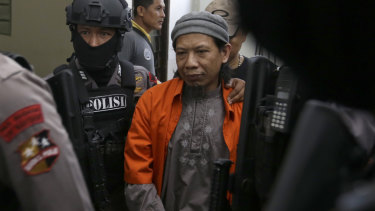 Aman Abdurrahman is escorted by police officers into court on Friday.