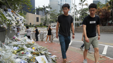 Pro-democracy activist Joshua Wong, left, is accompanied by Nathan Law as they visit a makeshift memorial to a protester who fell to his death when hanging a banner.