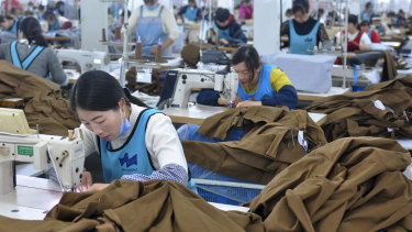 Workers sew clothing for export in Donghai county in east China's Jiangsu province. China's economic growth held steady in the latest quarter despite a tariff war with Washington, suggesting Beijing's efforts to reverse a slowdown might be gaining traction.