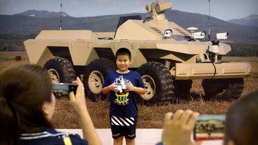 A boy poses for smartphone photos in front of a mural of a mobile tactical robot.