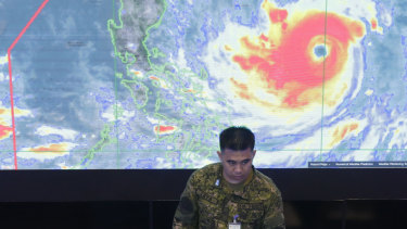 A member of the Philippine Air Force stands in front of a satellite image of Typhoon Mangkhut, locally named Typhoon Ompong, at the National Disaster Risk Reduction and Management Council operations center in Manila.