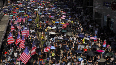 Protesters, some carrying US flags march on a street in Hong Kong.