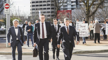 Witness K's lawyer Haydn Carmichael (far left) and Mr Collaery's barrister (far right) pass protesters as they arrive at court on Wednesday.