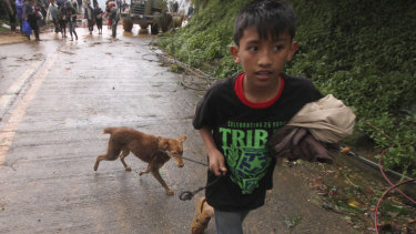 A boy evacuates to safer ground with his pet dog as workers try to clear a landslide that occurred in Itogon township, Benguet province in the northern Philippines.
