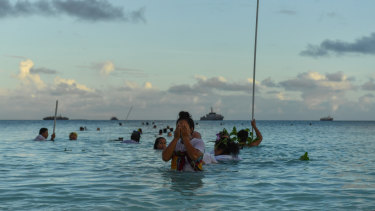 Locals demonstrate traditional fishing practice to round up fish to be cooked on an umu (traditional earth oven) by the lagoon in Funafuti, Tuvalu, on Thursday.