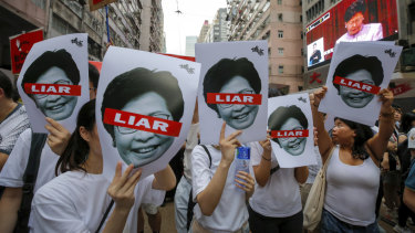 Protesters hold pictures of Hong Kong Chief Executive Carrie Lam as protesters march along a downtown street against the proposed amendments to the  extradition law.