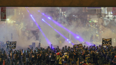 Riot policemen firing tear gas to protesters on a street during the anti-extradition bill protest in Hong Kong.