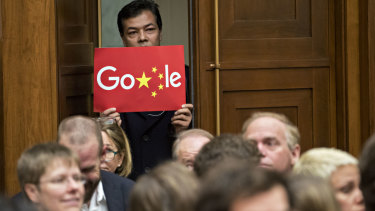 A man holds up a sign of an altered Google logo during a House Judiciary Committee hearing with Sundar Pichai, Google CEO, in Washington on Tuesday.