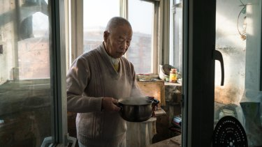 Han holds part of his breakfast, a pot of boiled soy milk, in his kitchen.
