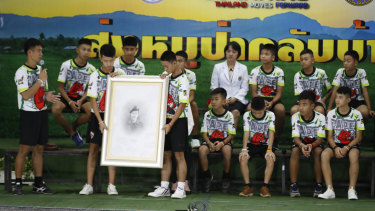 The soccer team shows their respect and thanks as they hold a portrait of Saman Gunan, the retired Thai SEAL diver who died during their rescue attempt.