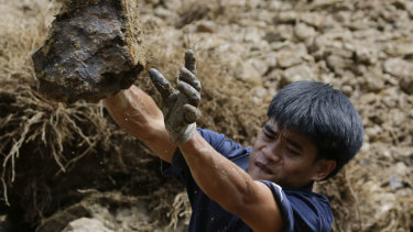 A gold miner moves a stone while searching for victims believed to have been buried by a landslide after typhoon Mangkhut barrelled across Itogon, Benguet province, northern Philippines on Monday.