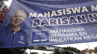Vehicles pass by a campaign poster of defeated Najib Razak on display along a street in Kuala Lumpur.