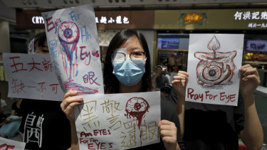 "People hold signs which read ""Black Police, Return eye,"" bottom centre, during the protest at the airport's arrival hall."