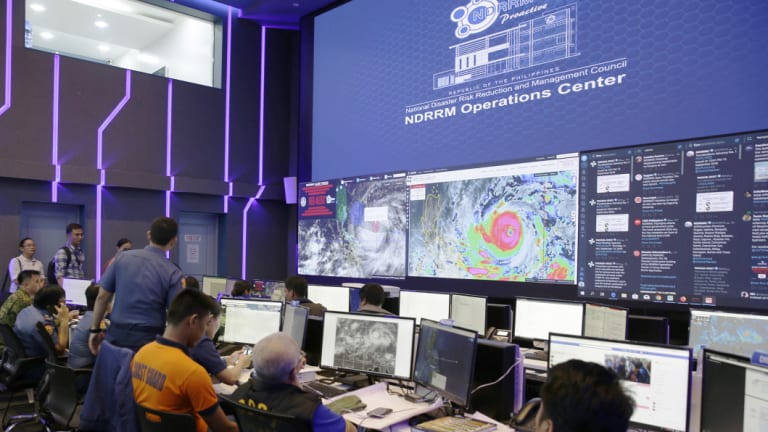 """Images of typhoon Mangkhut, locally named """"Typhoon Ompong"""" are seen at the National Disaster Risk Reduction centre in Manila."""