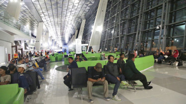 Passengers wait for their flights on the first day of operation of a new aiport terminal in Jakarta in 2016.