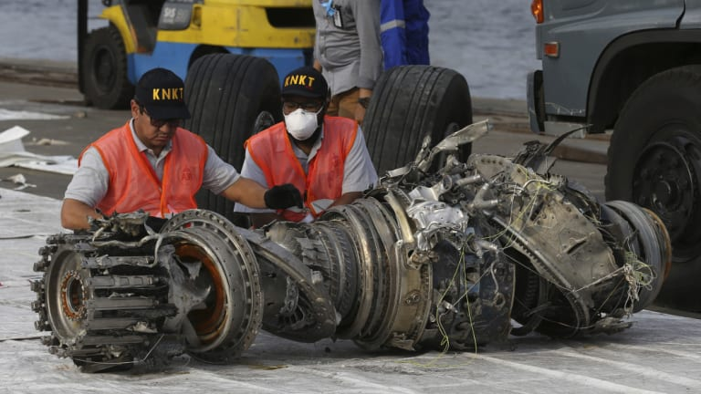Officials inspect an engine recovered from the crashed Lion Air jet on Monday in Jakarta, Indonesia.