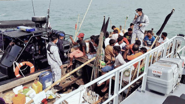 Malaysian navy officers detain a boat carrying Rohingya migrants off Langkawi, Malaysia, last week.