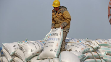 A worker in China's Jiangsu province unloads soy beans, one of hundreds of products to be slapped with tariffs.