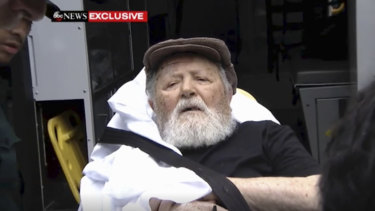 Jakiw Palij, a former Nazi concentration camp guard, is carried on a stretcher from his home.