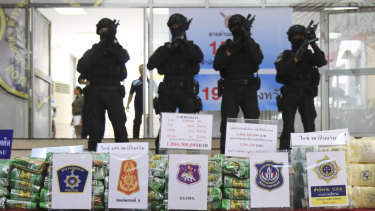 Thai policemen stand in front of packages of seized methamphetamines in Bangkok.