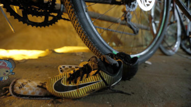 A pair of soccer boots lie next to bicycles from a group of missing boys at the entrance of a deep cave in Chiang Rai, northern Thailand.