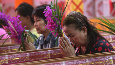Worshippers pray as they take turns sitting in coffins at the Takien temple in Thailand.